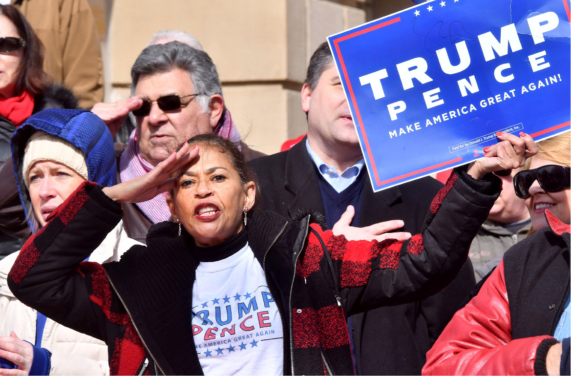 Retired Detroit Police officer Sharon Drew salutes during the Pledge of Allegiance at the Pro-Trump demonstration on the lawn of the Capitol in Lansing, Mich., on Saturday, March 4, 2017. (Dale G Young /Detroit News via AP)