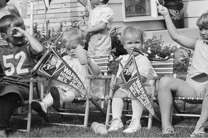 Kelly Jo, left, and her twin sister, Kris Kay, daughters of Mr. and Mrs. Ivo  Kramer, wave flags honoring hometown hero astronaut Neil Armstrong after the Apollo 11 launching on July 16, 1969 in Wapakoneta, Ohio. Armstrong, who is scheduled to be the first human to step on the moon, is from Wapakoneta, Ohio. The children are neighbors of Armstrong?s parents in Wapakoneta. (AP Photo/GEH)