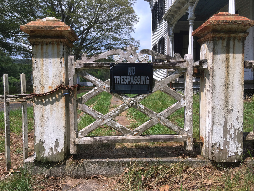 In this Wednesday July 12, 2017 photo, a sign declares no trespassing allowed in an abandoned house on the grounds of a long-abandoned, 62-acre village in East Haddam, Conn. Iglesia Ni Cristo, a fast-growing Filipino church, purchased the deteriorating collection of Victorian-style buildings to be repurposed for use by the religious group. (AP Photo/Michael Melia)