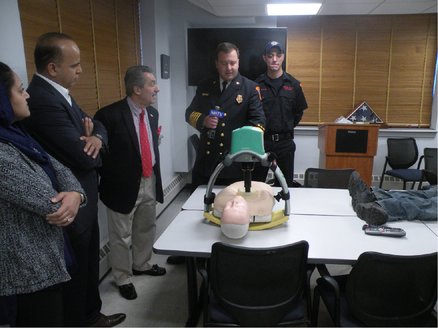 North Haven Fire Chief Paul Januszewski demonstrates the Lucas Chest Compression System, which was donated to the town by resident Tariq Farid, second from left. | Ken Liebskind, The North Haven Citizen