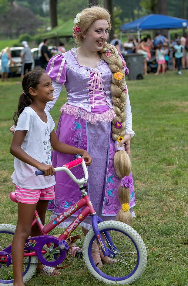 Safaa Ahmad, 10, of Meriden, poses for a photo with, Rapunzel, played by Kari Collins of E. Haven, during the 14th annual National Night Out at Hubbard Park in Meriden, Tuesday, August 7, 2018. Dave Zajac, Record-Journal