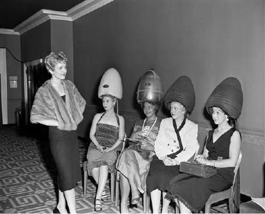 "Four hairdressers attending the National Beauty Trades Show in New York ""cool off"" under hair driers in an air-conditioned room at the Hotel Statler on Sept. 1, 1953 while Erma Van Wort, in a sable cape, shows them a new mobile coiffure. The hair driers' temperature is a mere 90 degrees, while the official thermometer outdoors measured 97. The new hairdo, achieved with free-flowing waves, is designed to direct eyes to the head - whatever the length of the controversial hemline. The hairdressers are members of the National Hairdressers and Cosmetologists Association. (AP Photo/Carl Nesensohn)"