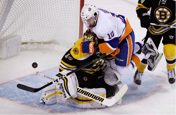 New York Islanders center Alan Quine (10) slams into Boston Bruins goalie Tuukka Rask (40) as he leaps out of the way from a shot on net during the first period of an NHL hockey game in Boston, Tuesday, Dec. 20, 2016. (AP Photo/Charles Krupa)