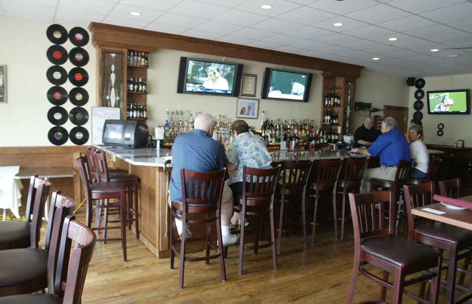 Three large screen televisions along with old records and photographs adorn the walls of the lounge at the Popular Restaurant in Southington on July 6, 2006.