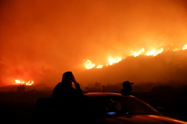 Two spectators watch as a wildfire burns along the 101 Freeway Tuesday, Dec. 5, 2017, in Ventura, Calif. Raked by ferocious Santa Ana winds, explosive wildfires northwest of Los Angeles and in the city