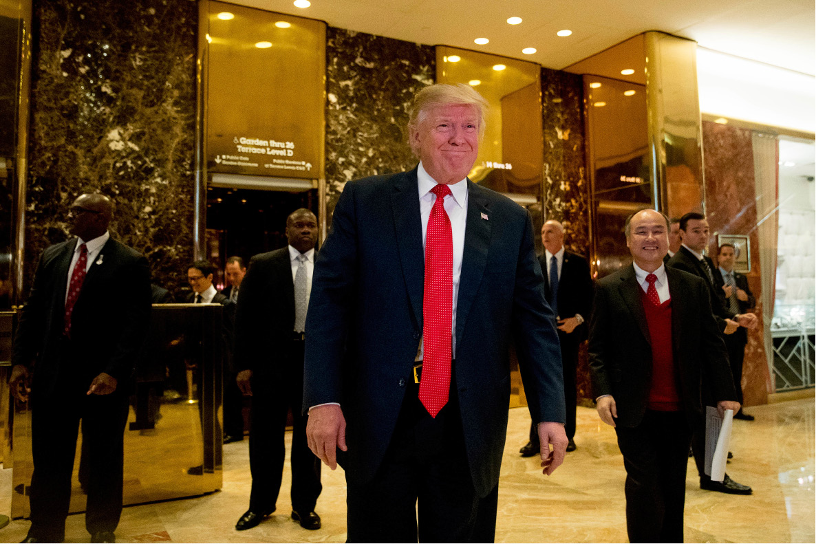 President-elect Donald Trump and SoftBank CEO Masayoshi Son, right, walk into the lobby to speak to members of the media at Trump Tower in New York, Tuesday, Dec. 6, 2016. (AP Photo/Andrew Harnik)