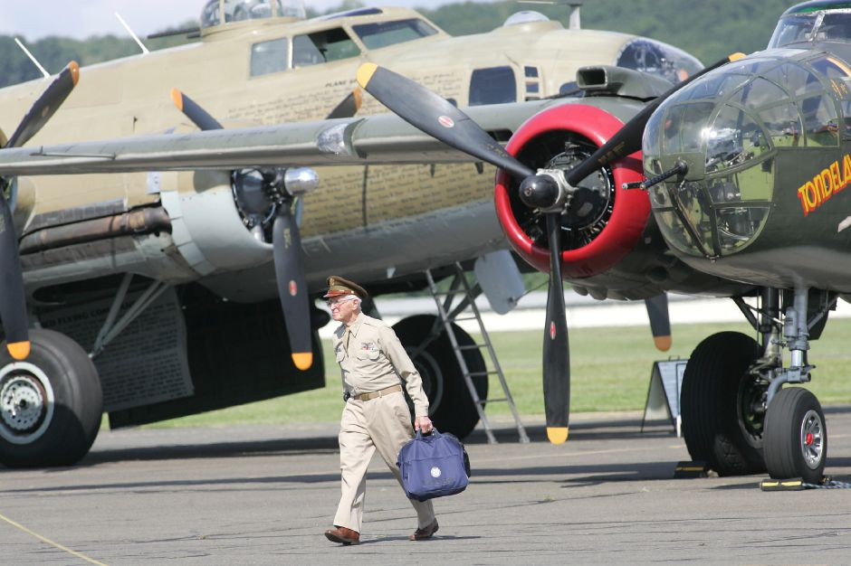Walter Hushak of Southington walks towards the main gate of the airport at the Oxford Airport just after landing in the B-25 which is behind him on the right. On the left is the B-17. He had just been flown from Stratford to Oxford in the B-25.