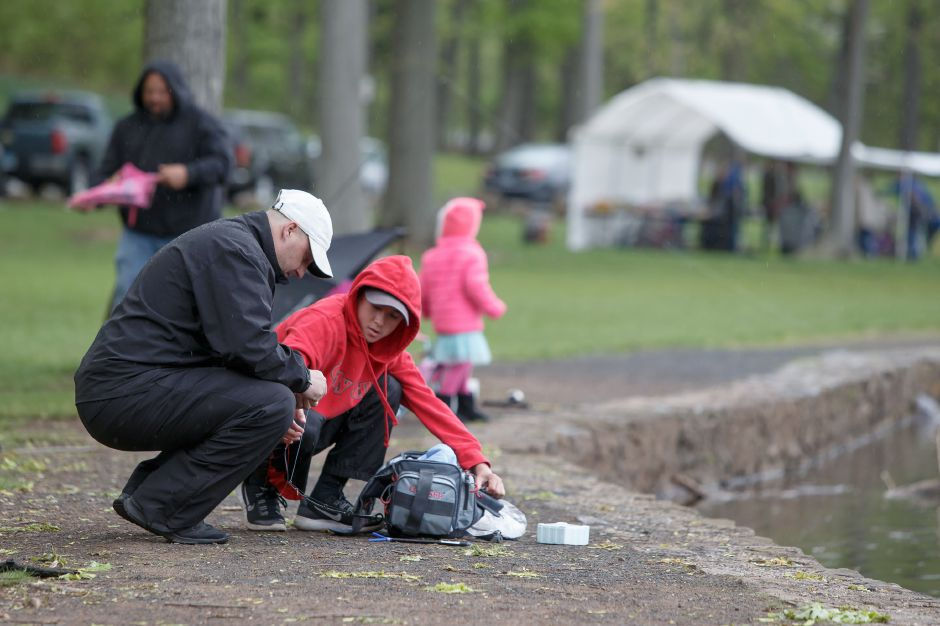 Scott Chaivanik of Bristol helps his son Tyler find a lure during last year's Meriden fishing derby at Mirror Lake. | Justin Weekes / Special to the Record-Journal