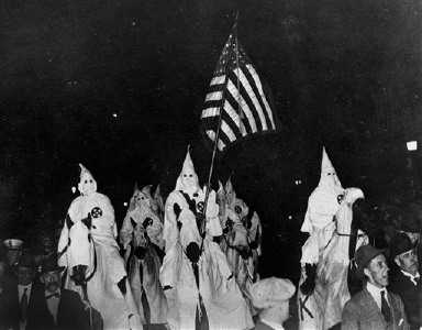 FILE - In this Sept. 21, 1923 file photo, members of the Ku Klux Klan ride horses during a parade through the streets of Tulsa, Okla. Former Sheriff Bill McCullough, who tried to stop the parade, is at foreground left. John Hartvigsen, a flag scholar, says flags
