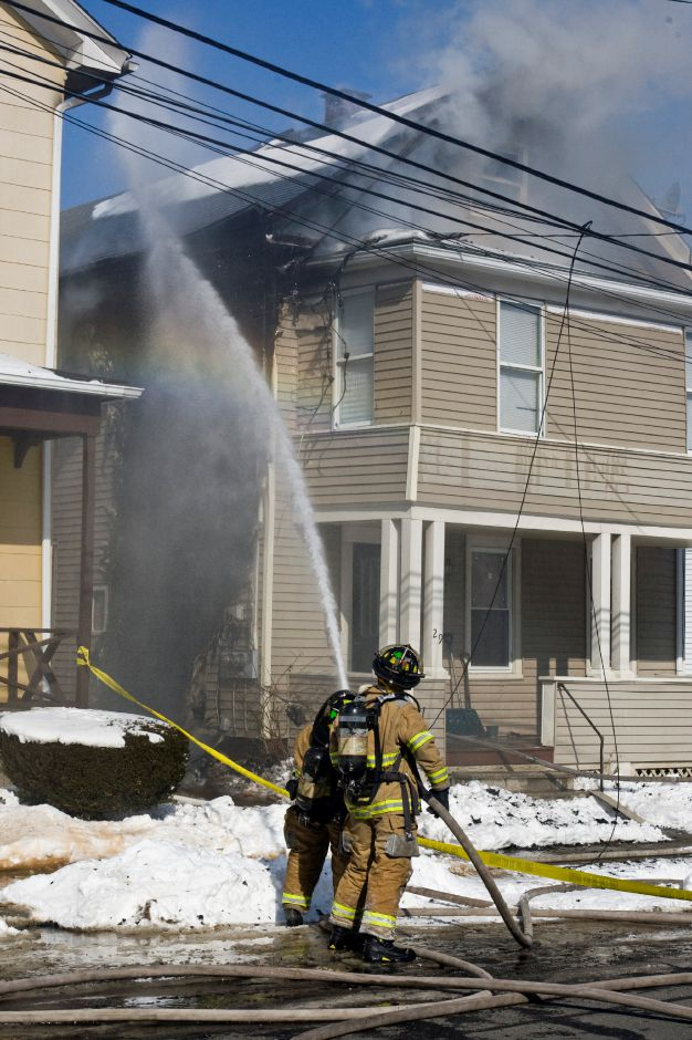 Fire fighters spray water onto the side of the burning house at 29 North First Street in Meriden, Wednesday morning, Mar. 4, 2009. Fire heavily damaged the house displacing the residents. (Christopher Zajac/Record-Journal)