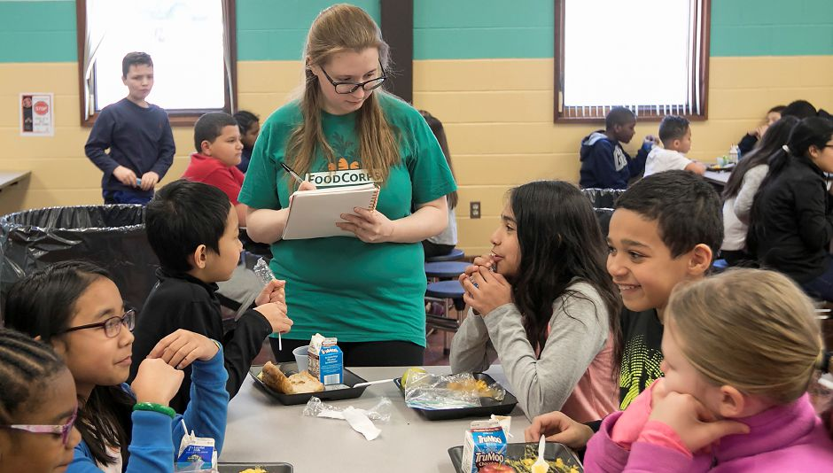 Tara Mahoney, a member of FoodCorps, asks nutrition questions to students during lunch break at Israel Putnam  School in Meriden in February.