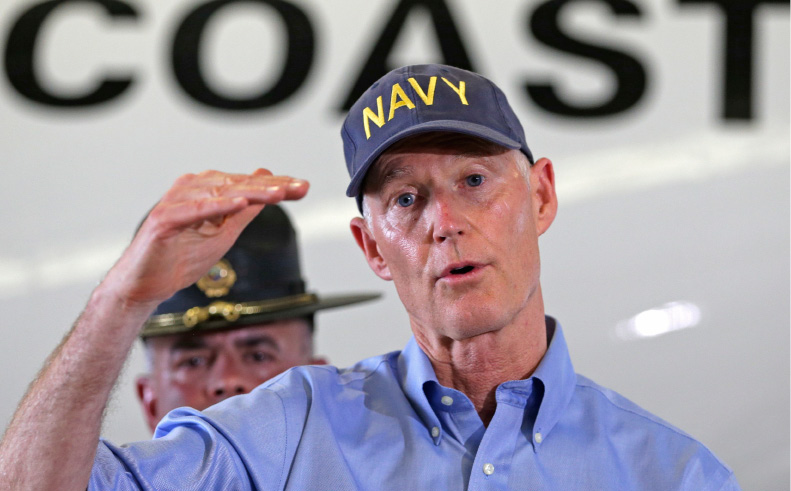 Gov. Rick Scott talks to reporters during a news conference, at the U.S. Coast Guard Air Station Miami, Monday, Sept. 11, 2017, in Opa-Locka, Fla. Gov. Scott flew over the Florida Keys to assess damage from Hurricane Irma. (AP Photo/Alan Diaz)