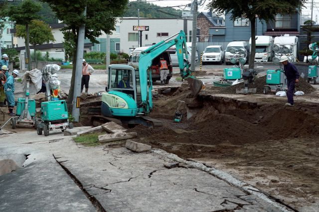 Workers repair a burst in the water pipe at an earthquake-damaged street in Kiyota, outskirts of Sapporo city, Hokkaido, northern Japan, Friday, Sept. 7, 2018. A powerful earthquake hit wide areas on Japan