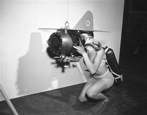 Gerald E. Darrab, Ph2, U.S.N., demonstrates the completely mobile 35 mm under-water motion picture camera which will be used by the U.S. Navy. It was at the U.S. Naval Photographic center Anacostia, Washington on Oct. 31, 1950. The camera will make the diver-photographer entirely independent on surface assistance and is designed so that it can be completely operated from the outside of the housing. External controls are provided for the lens diaphragm, focus, and starting switch. The unit has detachable wings and vertical rudder which aid in transporting and stabilizing the camera under-water. (AP Photo/Bill Allen)