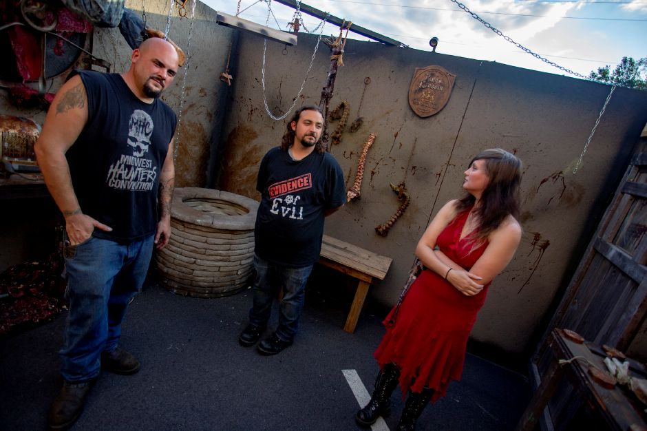 From left, Evidence of Evil owners Bobby Besaw and Dave Belas talk with actress Jess Bourbonniere as they continue preparing the haunted attraction for a Sept. 28 opening. | Richie Rathsack, Record-Journal
