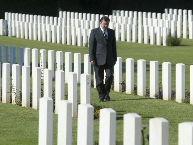 FILE - In this Sunday, June 6, 2004 photo then German Chancellor Gerhard Schroeder walks between tombstones on a war cemetery in Ranville, France. Soldiers from eight nations, including 322 from Germany, are buried on this cemetery. There's no denying that the machine guns and howitzers firing at the Allied forces landing in Normandy 75 years ago were manned by German soldiers. But over the decades, Germans' attitudes toward the war have evolved from a sense of defeat to something far more complex. (AP Photo/Jockel Finck, file)