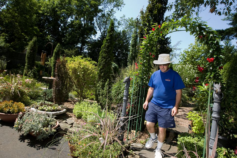 George Trecina, of Meriden, walks through his garden on Spring Street, Wednesday, August 24, 2016. From 10 a.m. to 4 p.m. Saturday, Trecina will host a viewing of his garden as part of the Garden Conservancy's Open Days program. | Dave Zajac, Record-Journal