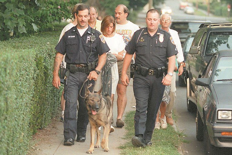 RJ file photo - Members of the Washington Park Neighborhood Association, led by K-9 Police Officer Mark Masse, left, with Gator, and Mike Lane, right, walk down Liberty Street to pick up trash during National Night Out Aug. 4, 1998.