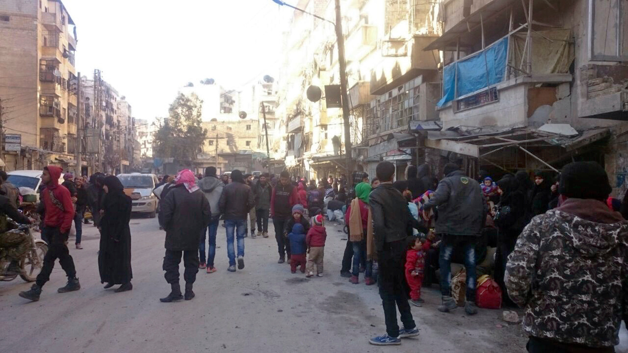 Eastern Aleppo residents wait in the streets to be evacuated from the war-torn city of Aleppo, Syria, Thursday, Dec. 15, 2016. Residents in eastern Aleppo are starting to board buses and ambulances as the long-awaited pullout from the last rebel enclave in the embattled city gets underway. The evacuation is part of a cease-fire deal reached this week to have the opposition surrender their last foothold in Aleppo to Syrian government control in the face of a devastating ground and air offensive by government forces. (UGC via AP)