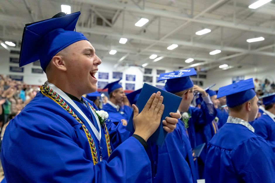 Students cheer after moving their tassels to the left during the Plainville High School graduation ceremony, held in the school