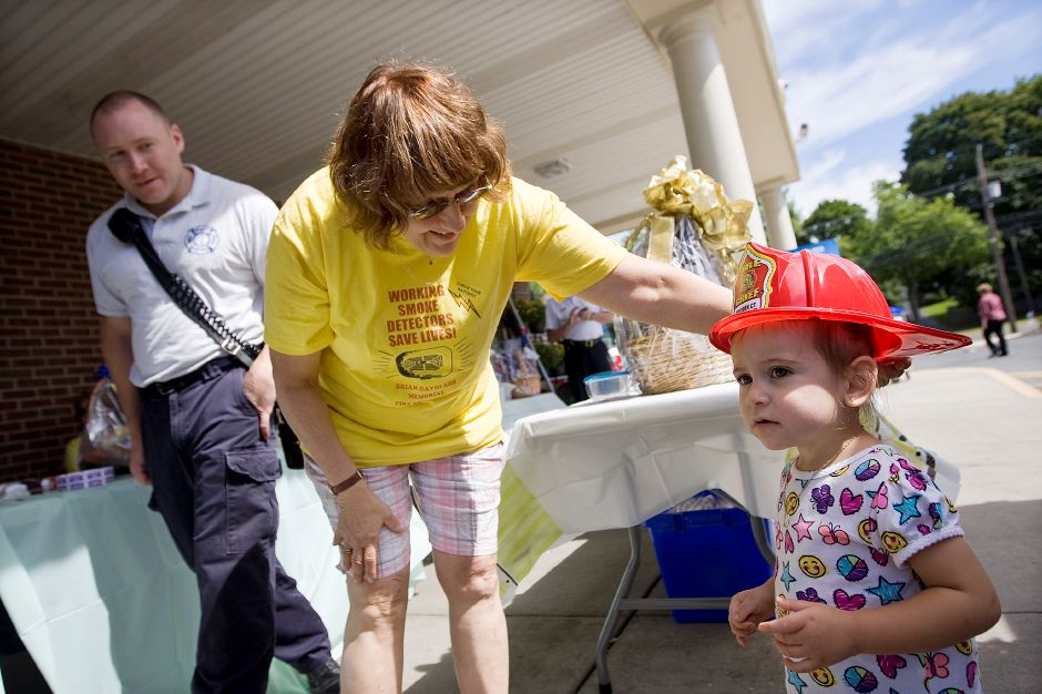 Riley Rosa, 1, of Meriden, gets a fire chief hat from Roberta Ash, of Meriden, during the 27th annual Brian David Ash Fire Prevention fundraiser at Stop & Shop in Meriden, Friday, September 7, 2013. The three day event, which runs Friday, Saturday and Sunday 9 a.m. to 8 p.m. raises funds for fire prevention and safety awareness in Meriden. Proceeds are used to purchase pamphlets, films, smoke detectors, batteries and carbon monoxide detectors. At left is Lt. Brendan Noonan of Meriden