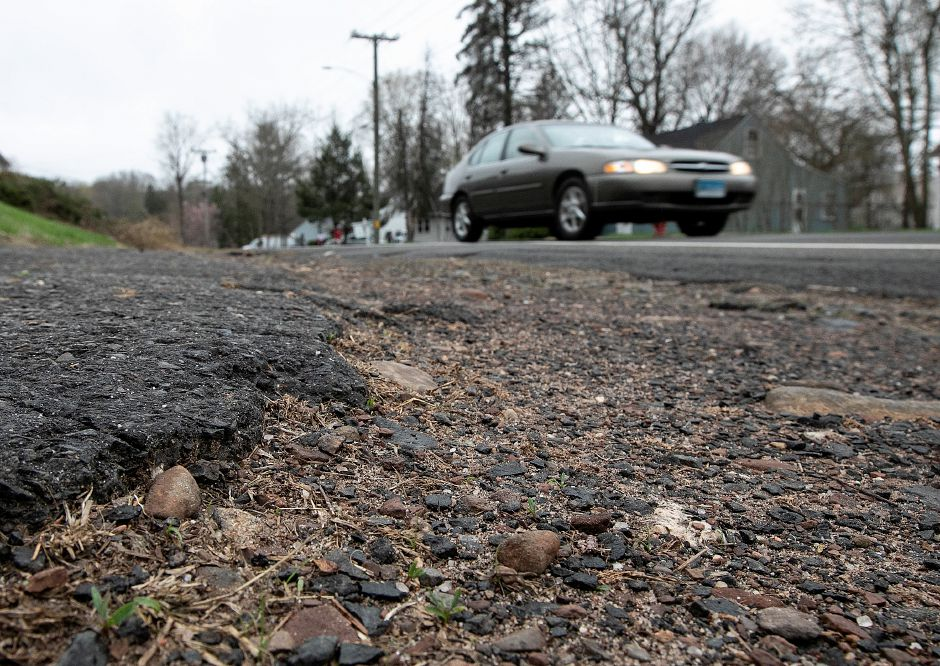 A motorist travels past a sidewalk in disrepair on Coe Avenue in Meriden on Thursday. The city has received a $400,000 grant from the state Department of Transporation to extend the Hanover Pond Trail from behind Platt High School onto Coe Avenue. The trail will replace the existing sidewalk along Coe Avenue. Dave Zajac, Record-Journal