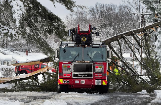 A tree branch fallen from the weight of heavy snow lies on top of a fire truck in East Hartford, Conn., Thursday, March 8, 2018. The branch that fell took down live power lines and landed onto the truck as it was parked responding to a fire. No one was injured. Connecticut