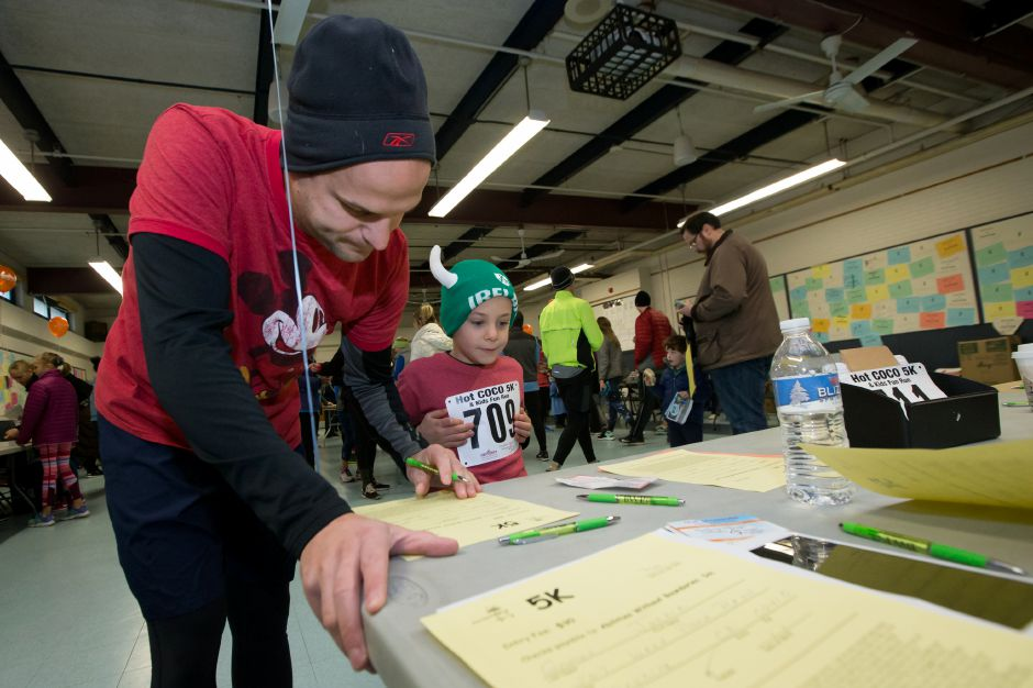 Jim Roscoe of Southington and son Parker 5 register Saturday during the Hot Coco 5K to benefit Abilities Without Boundaries at the Norton Elementary School in Cheshire November 18, 2017 | Justin Weekes / For the Record-Journal
