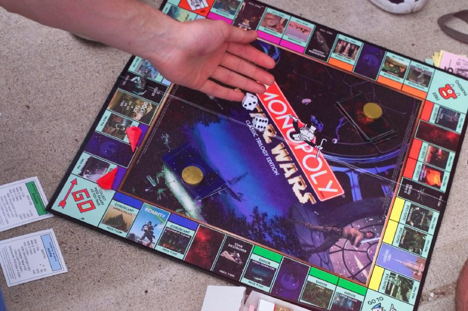 Waiting in line for Episode 1 tickets at Showcase Cinemas , a Star Wars fan roles the die on a Star Wars Monopoly game May 12, 1999. The Star Wars tetrology has spurred marketing frenzy.