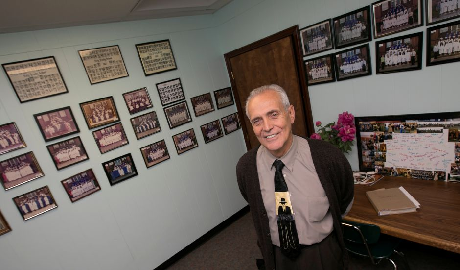 Longtime teacher Dom Forino stands among his many class photos at Holy Trinity School in Wallingford, Wednesday, Nov. 8, 2017. Forino has been teaching at Holy Trinity for 50 years. | Dave Zajac, Record-Journal