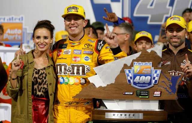 Kyle Busch (18) poses with the winners trophy and his wife, Samantha, as he celebrates winning the NASCAR Cup Series auto race in victory lane at Richmond Raceway in Richmond, Va., Saturday, Sept. 22, 2018. (AP Photo/Steve Helber)