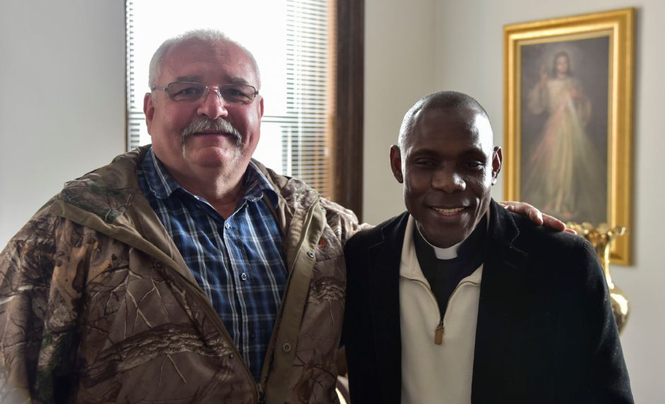Reinmann Motors and Antiques owner Tom Reinmann (left) poses with Rev. Kingsley Ihejirika in Ihejirika's office at Most Holy Trinity Church in Wallingford on April 26, 2018. Reinmann will hold a rummage sale at his business to raise money for a medical clinic Ihejirika is looking to building in his hometown of Obike, Nigeria. | Matthew Zabierek, Record-Journal