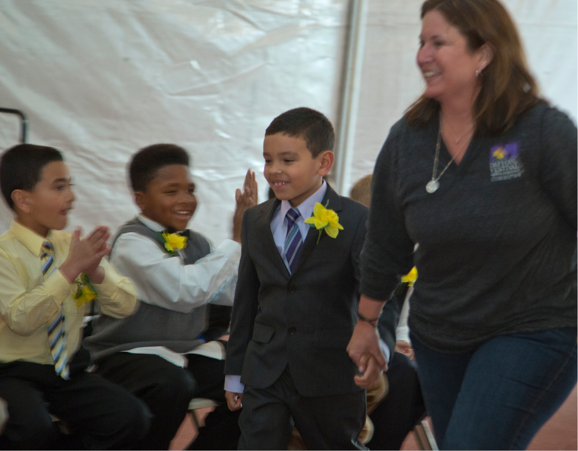 Christian Torres, 7, a student at Our Lady of Mount Carmel School, is escorted to the stage after he was choosen to be the Honor Escort to Little Miss Daffodil during the Wednesday evening ceremony at Hubbard Park in Meriden, April 24, 2013. (Christopher Zajac / Record-Journal)