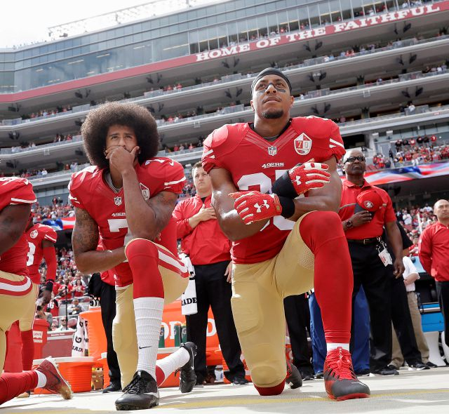 FILE - In this Oct. 2, 2016 file photo, San Francisco quarterback Colin Kaepernick, left, and safety Eric Reid kneel during the national anthem before an NFL football game against the Dallas Cowboys in Santa Clara, Calif.  The 49ers won