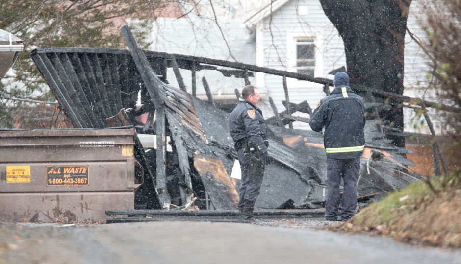 A Meriden Police officer and firefighter stand in front of a garage which was severely damaged by fire Saturday morning. No injuries were sustained in the fire, which firefighters responded to at around 6:03 a.m. Devin Leith-Yessian | Record-Journal