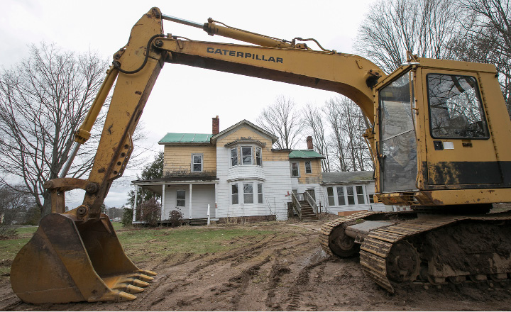 An excavator parked in front of the former Ives homestead next to Bartlem Park in Cheshire, Friday, April 7, 2017. Preservationists are hoping to save the late-19th-century house.  |  Dave Zajac, Record-Journal