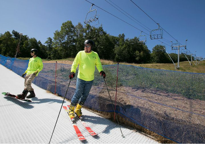Tom Loring, training center director, center, and Jordan Newth, trail crew, left, prepare for a test run on the new 365 Synthetic Snow Park trail at Powder Ridge Mountain Park & Resort in Middlefield, Friday, Sept. 1, 2017. The park opens at noon on Saturday. | Dave Zajac, Record-Journal