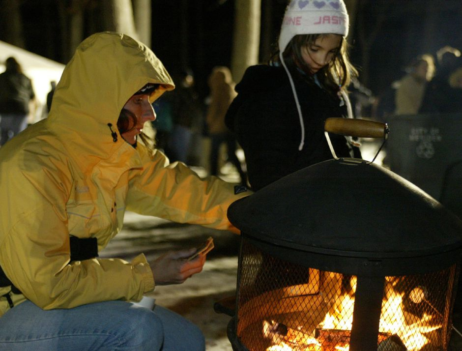 Cindy Greene, left, of Cheshire, makes smores with her daughter Jasmine, 7, by an outdoor fireplace in Hubbard Park during Christmas in the Park on Dec. 13, 2005.