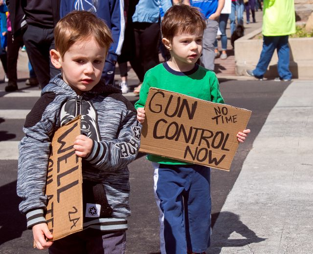 Four-year-old twins Eli, left, and his brother Nathan Hellman hold their signs during the