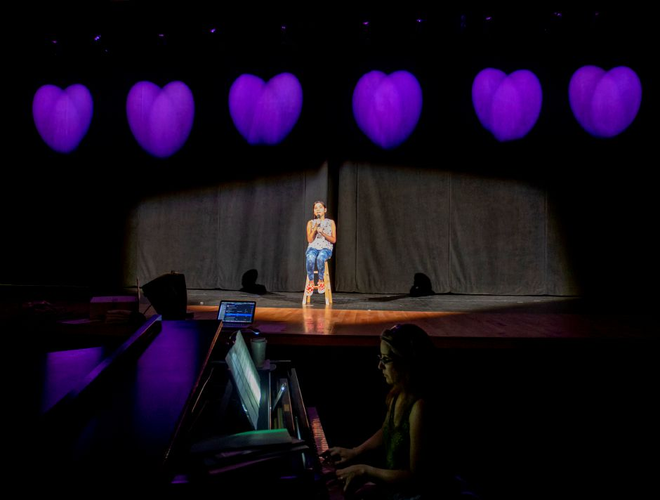 Jocelyne Barba, 12, sits alone singing on stage during a rehearsal with the Junior Performance Academy at Sheehan High School in Wallingford July 10, 2019. | Richie Rathsack, Record-Journal