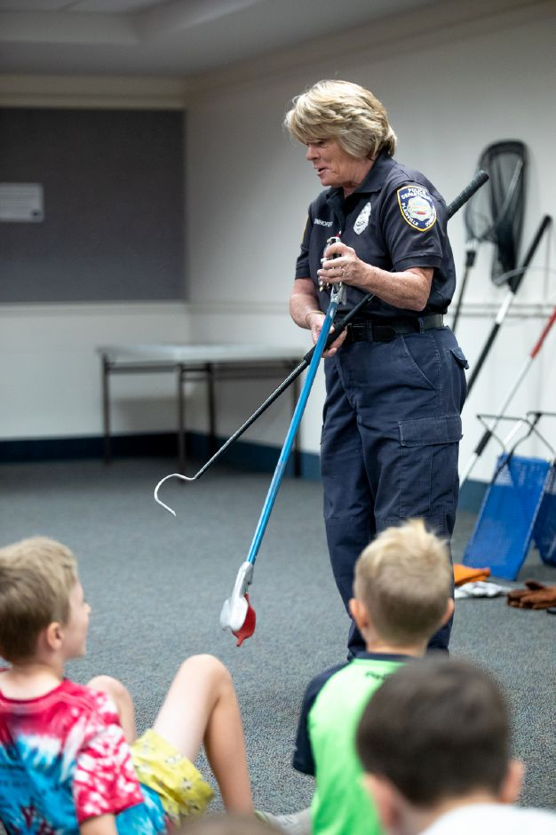 Plainville Animal Control Officer Donna Weinhofer shows a crowd of children some of the tools she uses to handle snakes. Weinhofer visited the Plainville Public Library Tuesday night to help families understand the animals which live around them. | Devin Leith-Yessian / Plainville Citizen