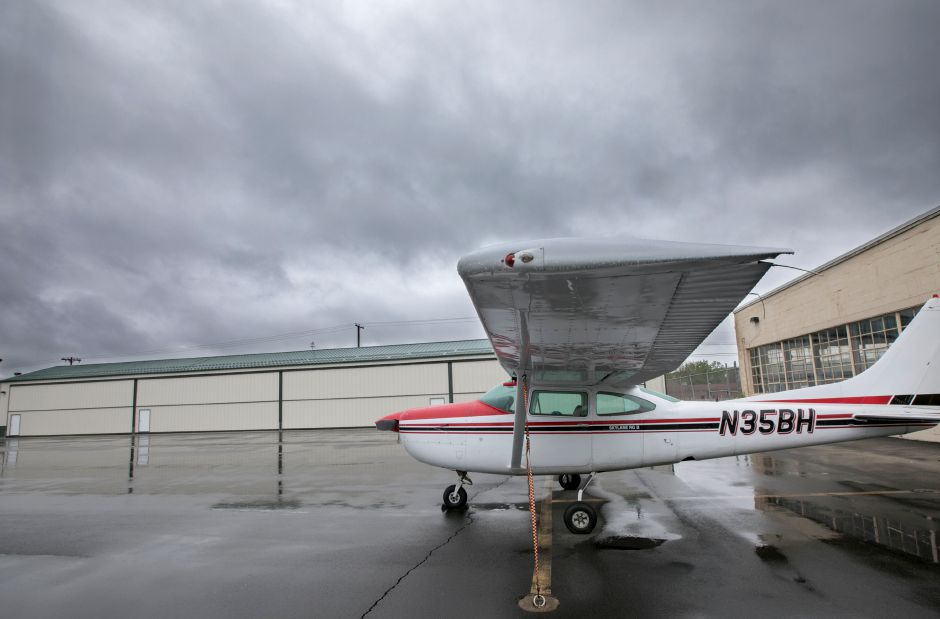 A plane tethered to the pavement next to recently constructed hangars, left, at Meriden Markham Airport, Monday, May 22, 2017. Construction could begin in upcoming weeks on new taxilanes which will connect the main runway to 16 new hangars to be constructed early next year. | Dave Zajac, Record-Journal