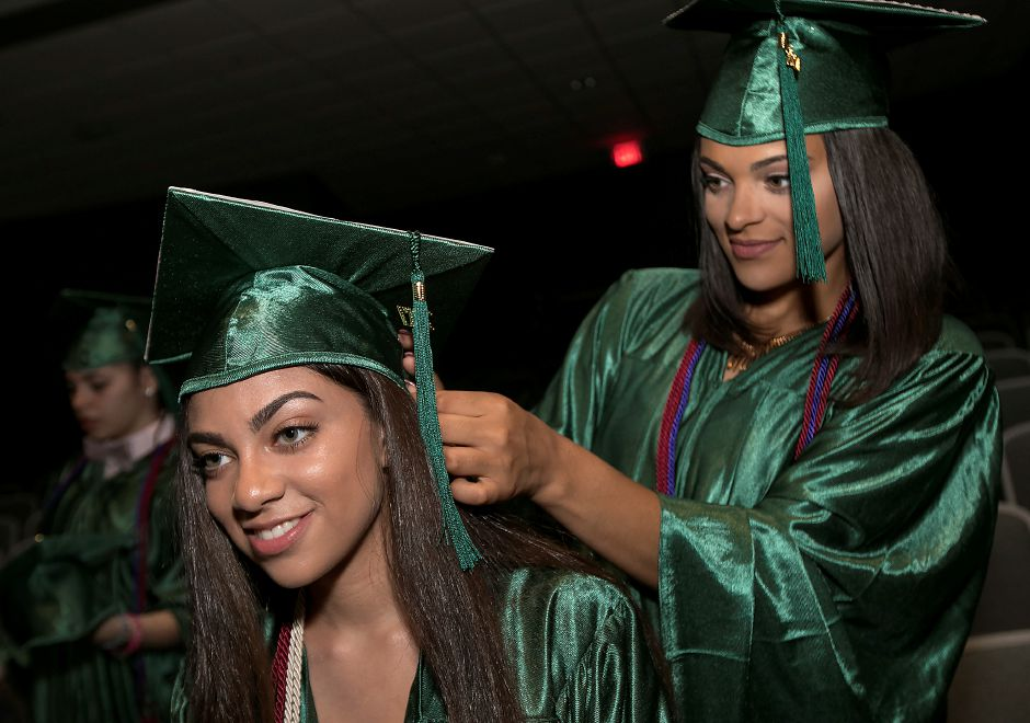 Jayden Fuqua, left, gets help with her cap from friend, Jalynne Nelson, before the start of graduation ceremonies at Maloney High School in Meriden, Tuesday, June 13, 2017. | Dave Zajac, Record-Journal
