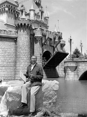 FILE - In this Sunday, July 17, 1955 file photo, Walt Disney sits on a rock in front of the Sleeping Beauty Castle in the Fantasyland section of Disneyland on opening day of the amusement theme park in Anaheim, Calif. A year earlier, Disney made his move. He succumbed to the lure of television and arranged to tie in the TV show (he hosted) with a Disneyland park. (AP Photo)