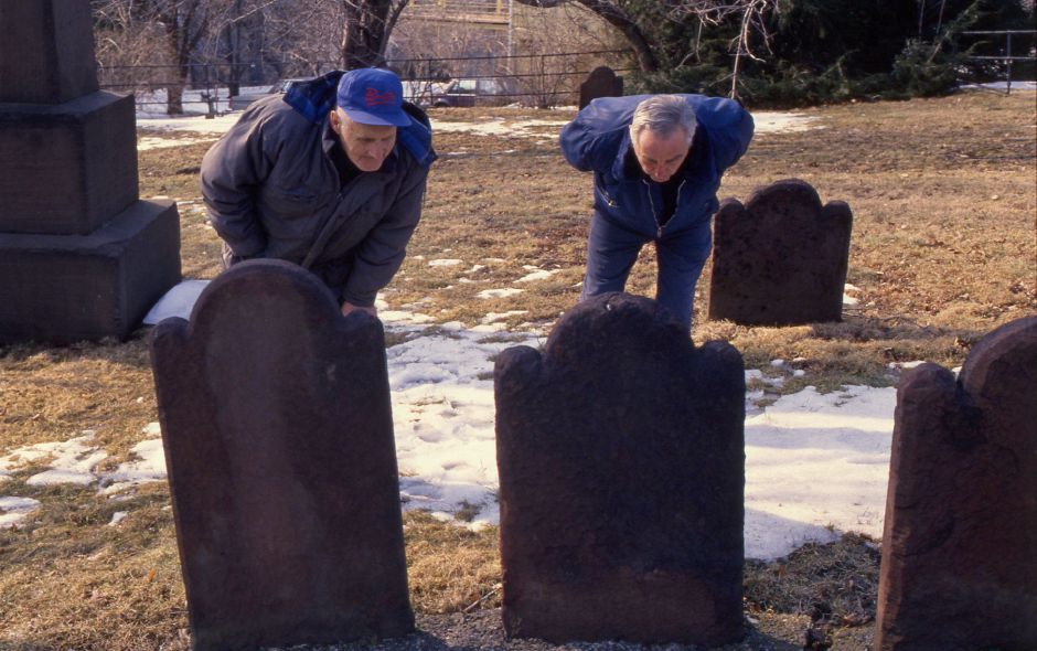 RJ file photo - Vincent Chodkowski, left, and Frank Peracchio study the old tombstones at Meeting House Hill Burying Grounds, March 14, 1994.
