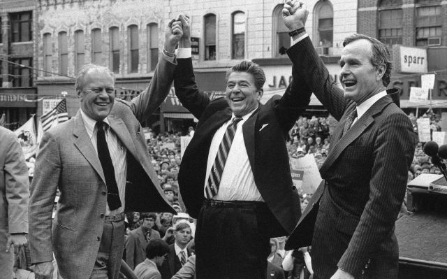 FILE - In this Nov. 3, 1980, file photo, former President Gerald Ford lends his support to Republican presidential candidate Ronald Reagan and his running mate, George H.W. Bush in Peoria, Ill. Bush has died at age 94. Family spokesman Jim McGrath says Bush died shortly after 10 p.m. Friday, Nov. 30, 2018, about eight months after the death of his wife, Barbara Bush. (AP Photo, File)