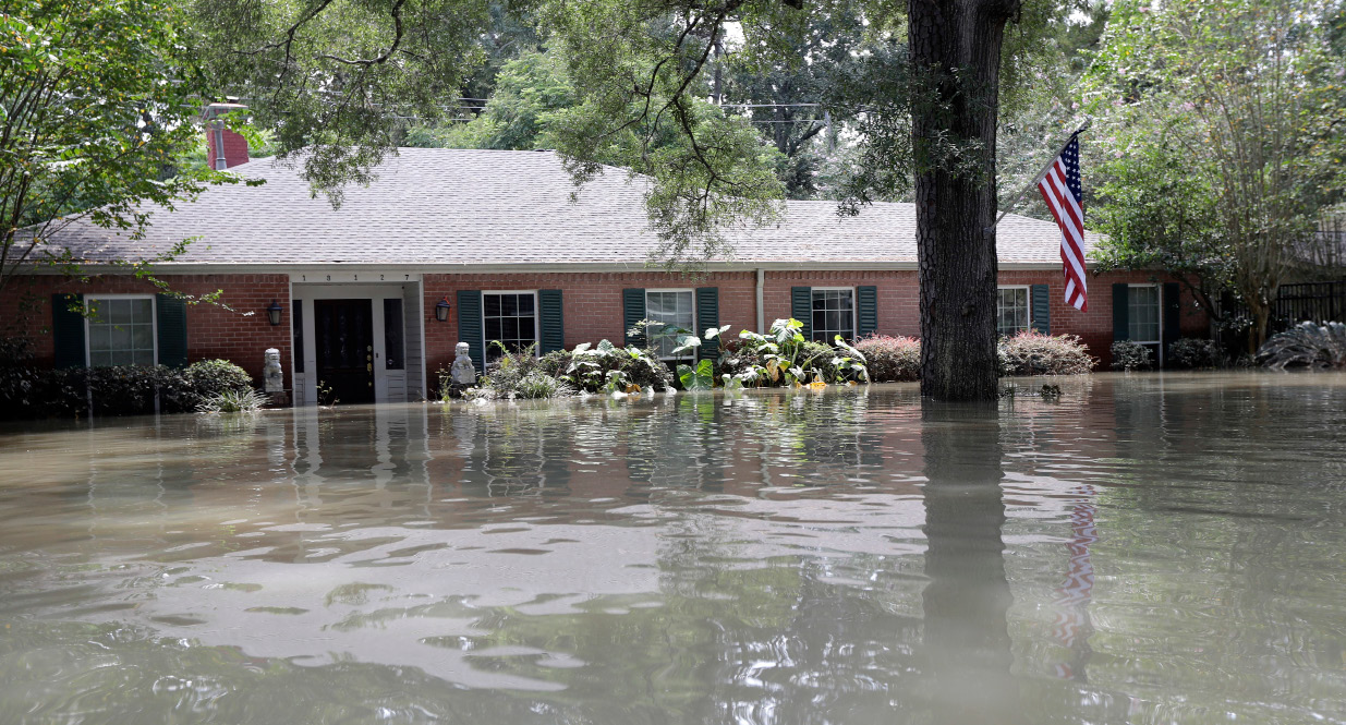 A United States flag hangs outside a flooded home in the aftermath of Hurricane Harvey, Monday, Sept. 4, 2017, near the Addicks and Barker Reservoirs in Houston. (AP Photo/David J. Phillip)