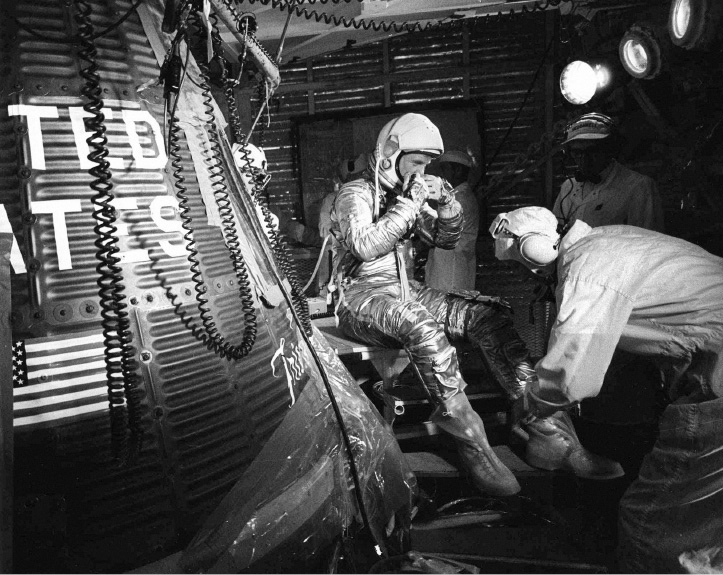 FILE - In this Feb. 20, 1962, file photo, astronaut John Glenn sits next to the Friendship 7 space capsule atop an Atlas rocket at Cape Canaveral, Fla., during preparations for his flight which made him the first American to orbit the Earth. Glenn, who later spent 24 years representing Ohio in the Senate, has died at 95. (AP Photo/File)