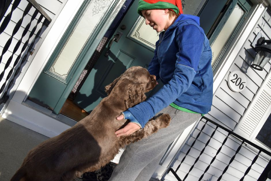 Local student Henry Bugai is greeted by a friendly dog while collecting donatoins door-to-door during the 13th annual Community Round-up in Durham and Middlefield on Saturday, Dec. 1, 2018. The event collected more than 13,000 food items and about $3,500 to go to Durham and Middlefield Social Services, and Amazing Grace in Middletown. | Bailey Wright, Record-Journal