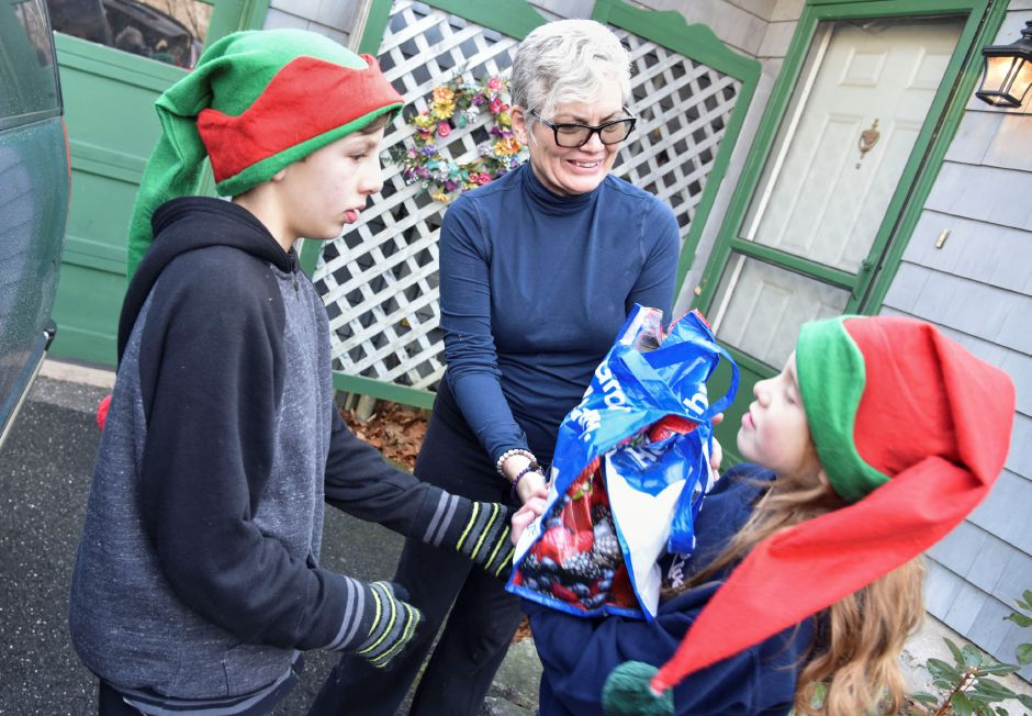 Resident Pamela Hull donates nonperishables to a collection team during the 13th annual Community Round-up in Durham and Middlefield on Saturday, Dec. 1, 2018. The event collected more than 13,000 food items and about $3,500 to go to Durham and Middlefield Social Services, and Amazing Grace in Middletown. | Bailey Wright, Record-Journal